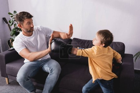 cute boy in boxing gloves fighting with father sitting on sofa