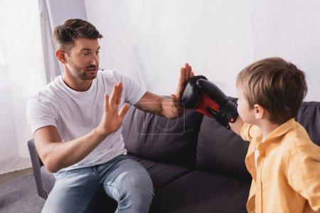 Photo pour Bel homme assis sur le canapé et se battant avec son fils portant des gants de boxe - image libre de droit