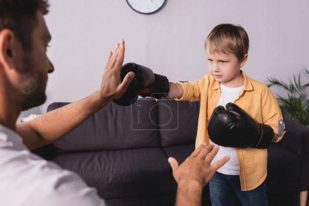 Photo pour Foyer sélectif de l'homme se battant avec son fils portant des gants de boxe - image libre de droit