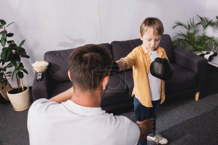 Photo pour Vue arrière de l'homme se battant avec son fils mignon dans des gants de boxe - image libre de droit