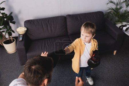 Photo pour Vue grand angle du garçon en gants de boxe se battant avec son père - image libre de droit