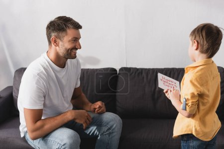 Photo for Happy father sitting on sofa near adorable son holding happy fathers day greeting card - Royalty Free Image