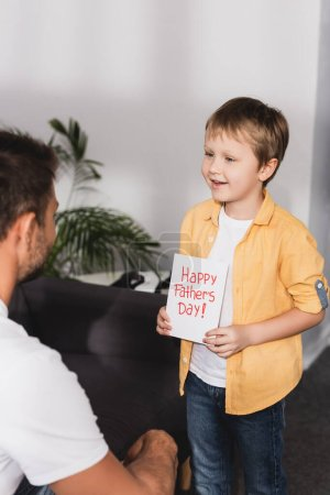 Photo for Smiling boy presenting happy fathers day greeting card to father - Royalty Free Image