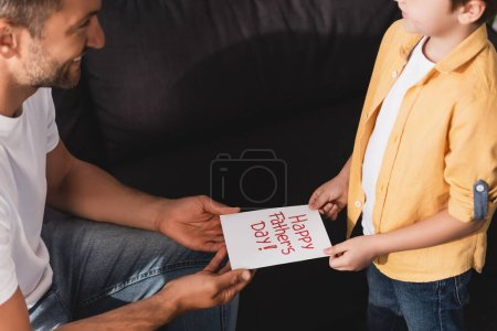 cropped view of man taking happy fathers day card from adorable son