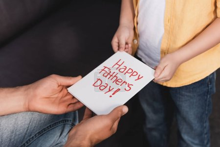 cropped view of boy presenting happy fathers day greeting card to father