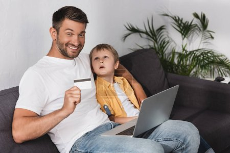 happy man showing credit card while sitting with laptop near adorable son