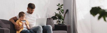 Photo pour Foyer sélectif de l'homme en utilisant un ordinateur portable et son fils tenant la carte de crédit tout en étant assis sur le canapé, image horizontale - image libre de droit