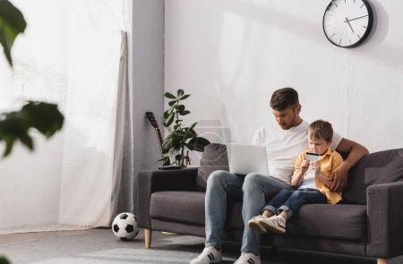 Photo pour Foyer sélectif de père en utilisant un ordinateur portable et son fils tenant la carte de crédit tout en étant assis sur le canapé à la maison - image libre de droit