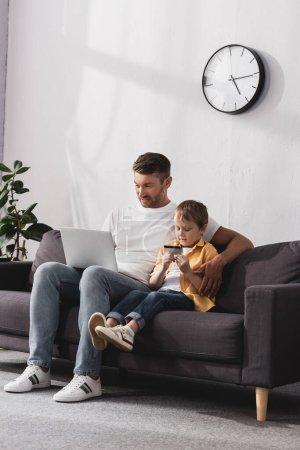 Photo pour Bel homme utilisant un ordinateur portable tandis que son fils mignon tenant la carte de crédit - image libre de droit