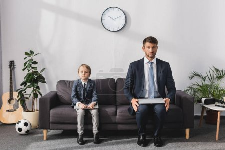 Photo pour Homme d'affaires sérieux et son fils en tenue formelle assis avec des ordinateurs portables sur le canapé à la maison et en regardant la caméra - image libre de droit