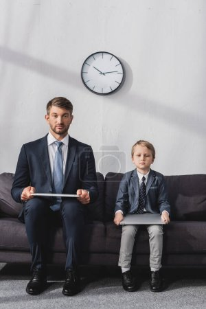 serious businessman and his son in formal wear sitting with laptops on sofa at home and looking at camera