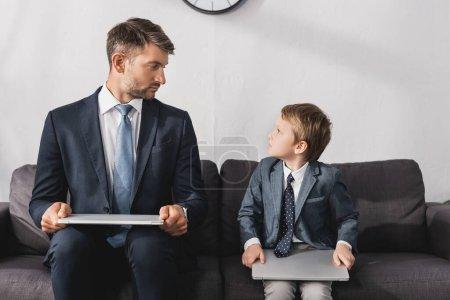 Photo pour Homme d'affaires sérieux et son fils en tenue formelle assis avec des ordinateurs portables sur le canapé à la maison - image libre de droit