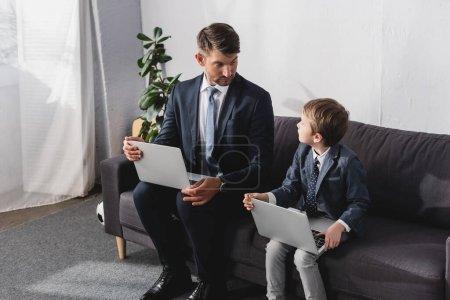 Photo pour Homme d'affaires sérieux avec son fils en tenue formelle assis sur un canapé avec des ordinateurs portables - image libre de droit