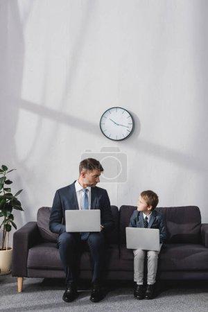 Photo pour Homme d'affaires sérieux et son fils en tenue formelle assis sur un canapé avec des ordinateurs portables et se regardant - image libre de droit