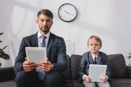 Photo pour Homme d'affaires sérieux et son fils en tenue formelle tenant des tablettes numériques tout en étant assis sur le canapé à la maison - image libre de droit