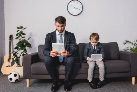 Photo pour Homme d'affaires concentré et son fils dans l'usure formelle en utilisant des tablettes numériques tout en étant assis sur le canapé à la maison - image libre de droit