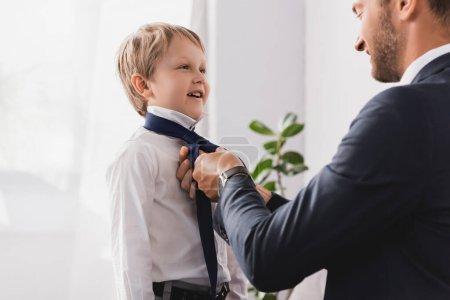 homme d'affaires en tenue formelle mettre cravate sur heureux fils à la maison