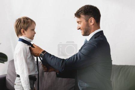 Photo pour Vue latérale de l'homme d'affaires en tenue formelle mettant cravate sur adorable fils à la maison - image libre de droit