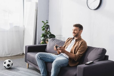 Photo for KYIV, UKRAINE - JUNE 9, 2020: cheerful man playing video game with joystick while sitting on sofa near soccer ball - Royalty Free Image