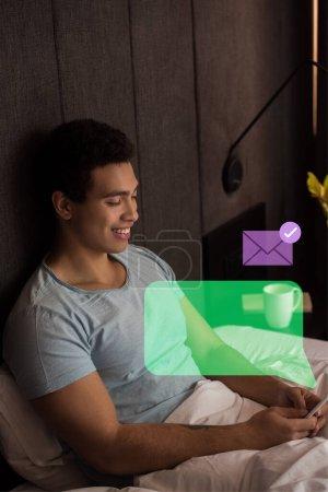 Photo pour Heureux mixte homme utilisant smartphone près de bulle vocale virtuelle et enveloppe dans la chambre - image libre de droit