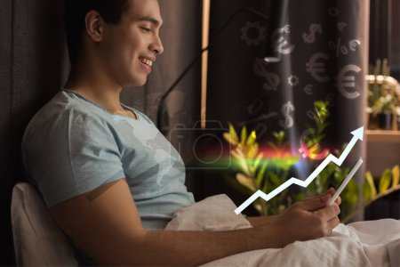 Photo for Smiling mixed race man using digital tablet in bed near virtual dollar and euro signs near graph with growing rate - Royalty Free Image