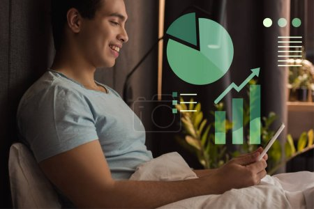 Photo for Smiling mixed race man using digital tablet in bed near charts and graphs illustration - Royalty Free Image