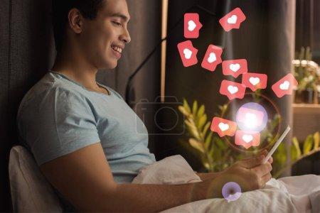 Photo pour Souriant mixte homme utilisant tablette numérique dans le lit près des cœurs virtuels comme illustration aime - image libre de droit