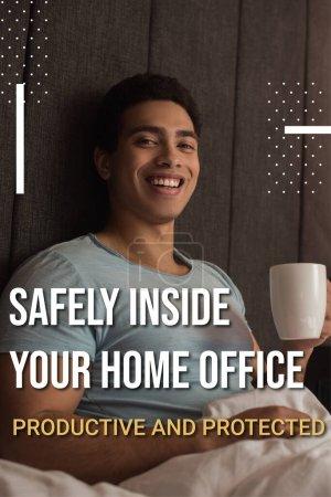 lächelnder Mann mit gemischter Rasse, der eine Tasse Kaffee in der Nähe sicher im Home Office hält, produktiver und geschützter Schriftzug im Schlafzimmer