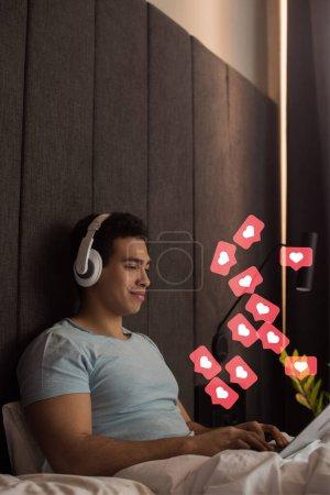 Zwei-Rassen-Mann hört Musik über Kopfhörer und nutzt Laptop in der Nähe virtueller Herzen wie im Schlafzimmer