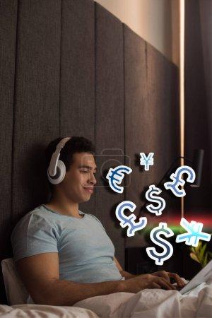 bi-racial man listening music in headphones and using laptop near virtual money signs