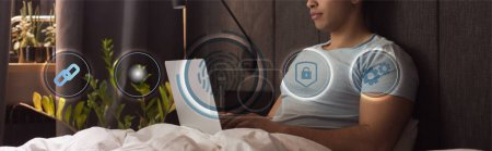 Photo for Panoramic crop of mixed race freelancer using laptop near virtual icons in bedroom - Royalty Free Image