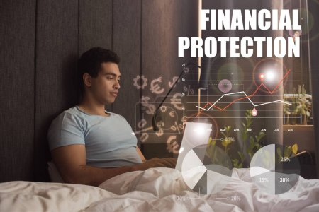 handsome mixed race freelancer using laptop near financial protection lettering, money signs, charts and graphs