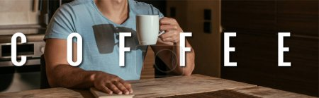 Photo for Panoramic orientation of man holding cup near book and coffee lettering at home - Royalty Free Image