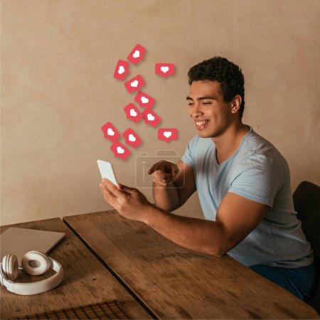 Photo pour Heureux mixte homme pointant du doigt smartphone, ordinateur portable, écouteurs et cœurs virtuels illustration - image libre de droit