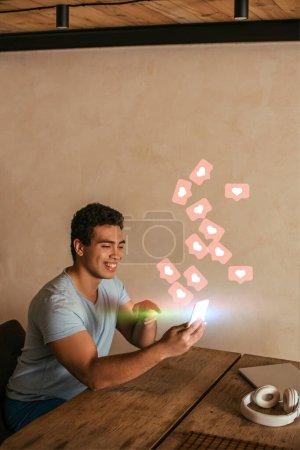 Photo pour Heureux mixte homme pointant du doigt smartphone, ordinateur portable, écouteurs et coeurs virtuels comme l'illustration aime - image libre de droit