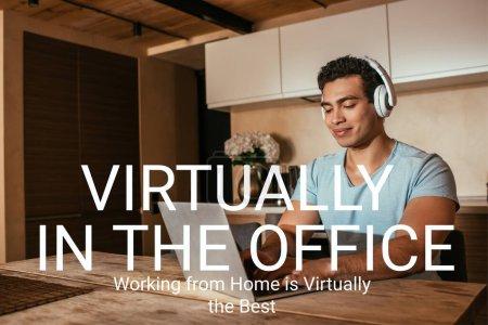 Photo pour Heureux mélange de race freelance écouter de la musique dans les écouteurs et à l'aide d'un ordinateur portable près de pratiquement dans le bureau, travailler à la maison est pratiquement le meilleur lettrage - image libre de droit