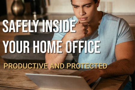 thoughtful mixed race freelancer looking at laptop near safely inside your home office, productive and protected lettering