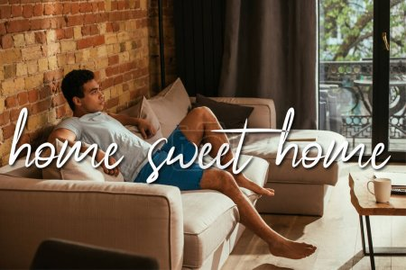 Photo for Handsome mixed race man sitting on sofa in living room near home sweet home lettering - Royalty Free Image