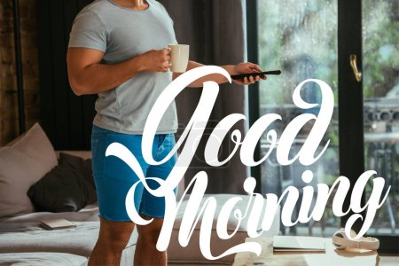 Photo for Cropped view of man with cup of coffee holding remote controller near good morning lettering - Royalty Free Image