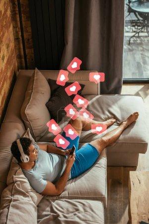 Blick aus der Vogelperspektive: Mischlingsmensch chillt, hört Musik und nutzt Smartphone in der Nähe virtueller Herzen