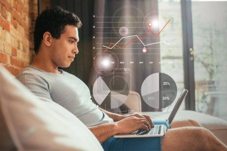 Photo for Selective focus of handsome young mixed race man working from home near charts and graphs illustration - Royalty Free Image