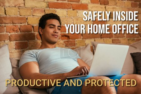 Photo for Young bi-racial man chilling with laptop on sofa near safely inside your home office, productive and protected lettering - Royalty Free Image