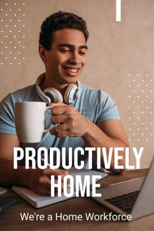 Photo for Happy mixed race man holding coffee cup while writing near laptop and productively home, were a home workforce lettering - Royalty Free Image