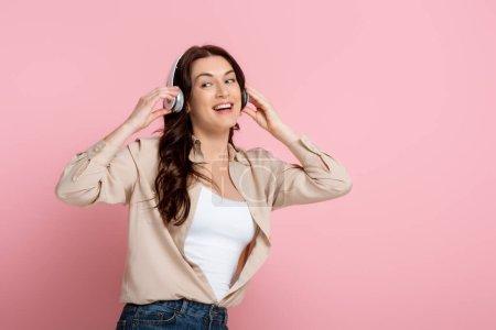 Photo pour Femme gaie dans les écouteurs regardant loin sur fond rose - image libre de droit