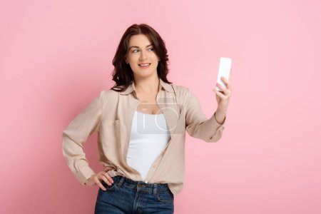 Photo for Beautiful brunette woman taking selfie with smartphone on pink background, concept of body positive - Royalty Free Image