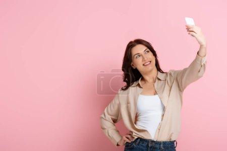 Photo pour Femme brune souriante posant tout en prenant selfie sur smartphone sur fond rose - image libre de droit