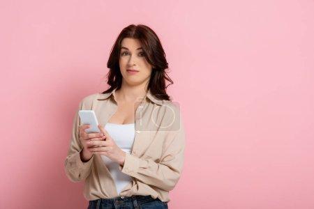 Photo pour Femme confondue utilisant un smartphone et regardant la caméra sur fond rose - image libre de droit