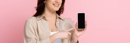 Photo for Panoramic crop of smiling woman pointing with finger at smartphone isolated on pink - Royalty Free Image