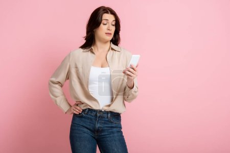 Photo for Skeptical woman with hand on hip using smartphone on pink background, concept of body positive - Royalty Free Image