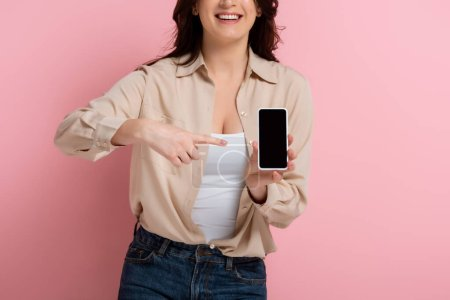 Photo for Cropped view of smiling woman pointing with finger at smartphone on pink background - Royalty Free Image